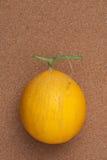 Melón amarillo en tablero del corcho Imagen de archivo libre de regalías