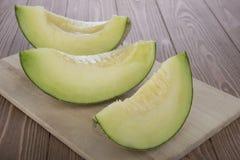 Melón cortado del cantalupo del melón del cantalupo encendido en tabla de cortar de madera y fondo de madera Foto de archivo libre de regalías
