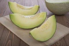 Melón cortado del cantalupo y medio melón del cantalupo encendido en tabla de cortar de madera y fondo de madera Imagen de archivo