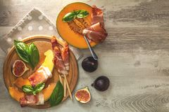 Melón del cantalupo cortado con el Prosciutto Aperitivo italiano imagenes de archivo