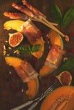 Melón del cantalupo cortado con el Prosciutto Aperitivo italiano foto de archivo