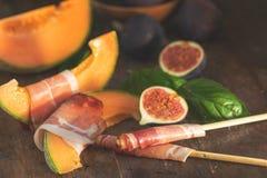 Melón del cantalupo cortado con el Prosciutto Aperitivo italiano fotografía de archivo