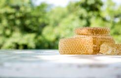 Mel claro fresco da abelha nas partes de favos de mel em uma tabela rústica de madeira branca com fundo do borrão Fotos de Stock