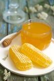 Mel em um frasco de vidro e mel nos favos de mel em um fundo de madeira velho Fotos de Stock