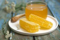 Mel em um frasco de vidro e mel nos favos de mel em um fundo de madeira velho Fotografia de Stock