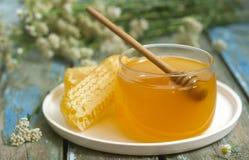 Mel em um frasco de vidro e mel nos favos de mel em um fundo de madeira velho Imagens de Stock Royalty Free