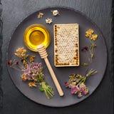 Mel, favo de mel e ervas secadas imagem de stock