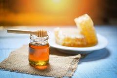 Mel no frasco com dipper de madeira e no favo de mel no alimento saudável natural da placa branca no fundo da tabela imagens de stock royalty free