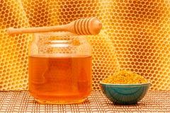 Mel no frasco com dipper, favo de mel e pólen dentro Foto de Stock
