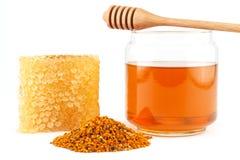 Mel no frasco com dipper, favo de mel, pólen no fundo isolado Imagens de Stock Royalty Free