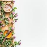 Mel no frasco com dipper, quadro do favo de mel e as flores selvagens no fundo branco, vista superior imagens de stock royalty free