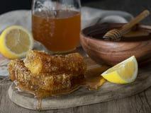 Mel no frasco com favo de mel e drizzler de madeira fotografia de stock