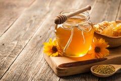 Mel no frasco e no favo de mel de vidro na tabela de madeira Imagem de Stock
