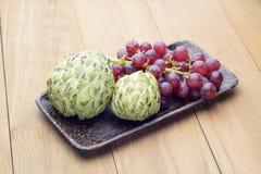 Mela cannella ed uva rossa in piatto di legno Fotografia Stock Libera da Diritti