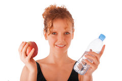 Mela della giovane tenuta femminile e bottiglia rosse della plastica di acqua Fotografie Stock