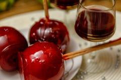 Mela di caramella rossa sul piatto e sul vetro ceramici del liquore della ciliegia immagine stock