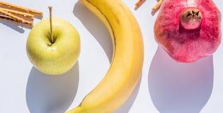 Mela dorata fresca, banana, melograno e bastoni salati su bianco Fotografia Stock