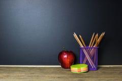 Mela e cancelleria rosse sulla tavola di legno con la lavagna Fotografia Stock