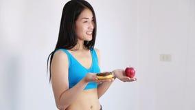 Mela e ciambella della tenuta della donna di forma fisica stock footage