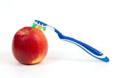 Mela e spazzolino da denti rossi freschi Fotografia Stock