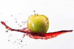 Mela e spruzzata verdi di succo rosso su fondo bianco Fotografia Stock Libera da Diritti