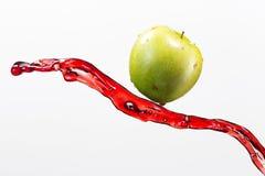 Mela e spruzzata verdi di succo rosso su fondo bianco Fotografie Stock Libere da Diritti