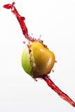 Mela e spruzzata verdi di succo rosso su fondo bianco Immagini Stock