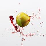 Mela e spruzzata verdi di succo rosso su fondo bianco Fotografie Stock