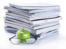 Mela e vetri verdi con la pila di libro e della rivista Fotografia Stock