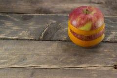 Mela ed arancia fresche sulla tavola di legno Fotografia Stock