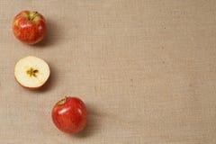 Mela fresca che si trova su una vecchia superficie marrone della tela di sacco fotografia stock