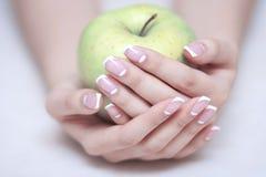 mela in mani della donna con il manicure francese Fotografia Stock Libera da Diritti