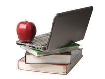 Mela rossa in cima al calcolatore ed ai libri Fotografia Stock