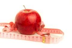 Mela rossa e nastro di misurazione su una priorità bassa bianca Immagine Stock