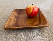 Mela rossa fresca sul piatto di legno Immagine Stock