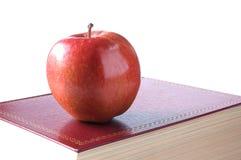 Mela rossa su un libro rosso II Immagine Stock Libera da Diritti