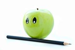 Mela verde con gli occhi e una matita Immagini Stock