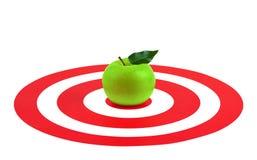 Mela verde con la foglia nel centro dell'obiettivo rosso Fotografie Stock