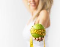 Mela verde con nastro adesivo giallo di misura fotografia stock