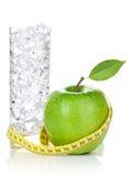 Mela verde fresca con nastro adesivo e bicchiere d'acqua di misurazione gialli Fotografia Stock