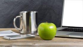 Mela verde su un vecchio desktop di legno dell'aula con tecnologia Fotografie Stock Libere da Diritti