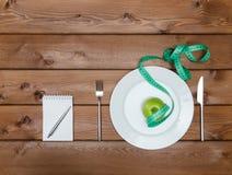 Mela verde sul piatto con la forcella del coltello e nastro adesivo di misura Immagini Stock