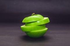 Mela verde tagliata ed isolata su fondo scuro Immagine Stock Libera da Diritti