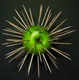 Mela verde in toothpicks isolati sul nero Immagini Stock