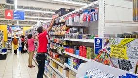 Arrange a item at mall. MELAKA, MALAYSIA - April 13, 2018 : Staff of Tesco Cheng arrange a stationary item at shelf rack display Royalty Free Stock Photography