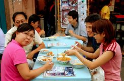 Melaka, Malaysia: Family Dining. A family enjoying Malaysian food at a small outdoor restaurant on popular Jonker Walk at the night market in Melaka, Malaysia stock photography