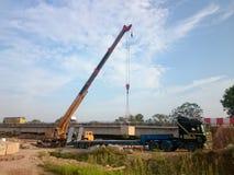 Crane lift a concrete block. MELAKA, MALAYSIA, Mac 29, 2018 : Crane lift a concrete block from trailer to construction site. Bridge construction at Lebuh Sungai Royalty Free Stock Images