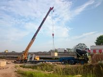 Crane lift a concrete block. MELAKA, MALAYSIA, Mac 29, 2018 : Crane lift a concrete block from trailer to construction site. Bridge construction at Lebuh Sungai Royalty Free Stock Image