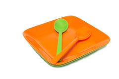 Melamine orange and green dish spoon set on white Royalty Free Stock Photos