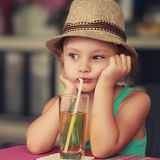 Melancholiac thinking kid girl in hat sitting in cafe and drinki Royalty Free Stock Photos